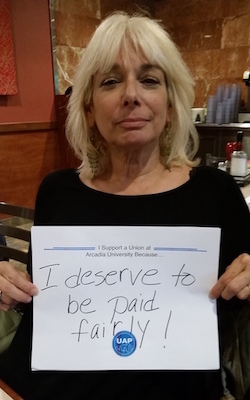 photo of Celeste Walker holding up a handwritten sign of support that says 'I deserve to be paid fairly'