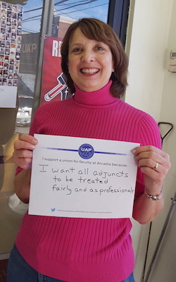 A photo of Gretchen Haertsch holding up a handwritten sign supporting the union that says 'I want all adjuncts to be treated fairly and as professionals'